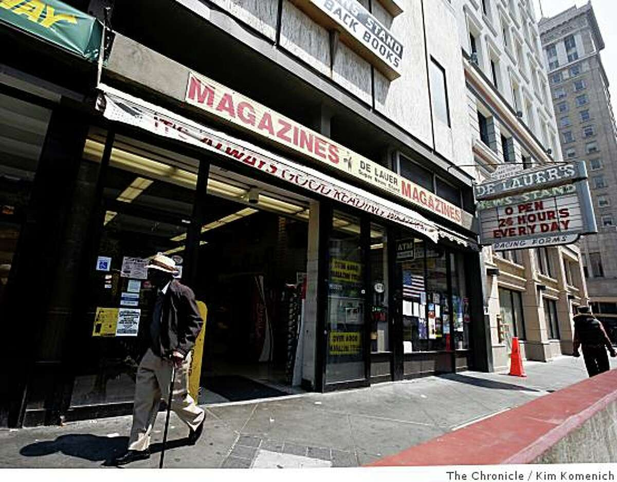 A pedestrian walks past DeLauer's Super Newsstand in Oakland, Calif., on Tuesday, June 24, 2008. Opened in 1907, DeLauer's, a downtown Oakland landmark that once was packed with newspapers, magazines and books from across America and beyond, is closing this week, a victim of the slow economy and Internet news sites.Photo by Kim Komenich / The Chronicle