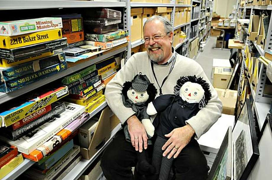 Tim Johnson, curator of special collections and rare books at the University of Minnesota Libraries, displays two dolls dressed as Sherlock Holmes and Dr. Watson in the Sherlock Holmes Collection Wednesday Nov. 23, 2009 in the Elmer L. Anderson Library at the University of Minnesota in Minneapolis. The two dolls are among more than 60, 000 items in the collection which houses just about everything and anything pertaining to Sherlock Holmes including original books and manuscripts from the early Holmes stories and pop culture items like the Sesame Street character Sherlock Hemlock.  (AP Photo/Dawn Villella) Photo: Dawn Villella, AP
