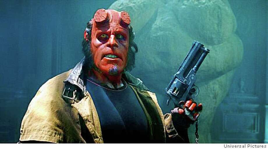 The world�s toughest, kitten-loving superhero, Hellboy (RON PERLMAN), prepares for duty in Hellboy II: The Golden Army.  Credit: Universal Pictures Photo: Universal Pictures