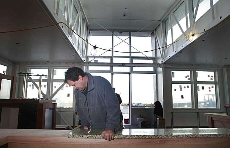 Latham Woodward, owner of Baker Marble and Granite, positions a recycled glass vetrazzo countertop being installed at the temporary facility for the Crissy Field Center in San Francisco, Calif. on Thursday December 24, 2009. Photo: Lea Suzuki, The Chronicle