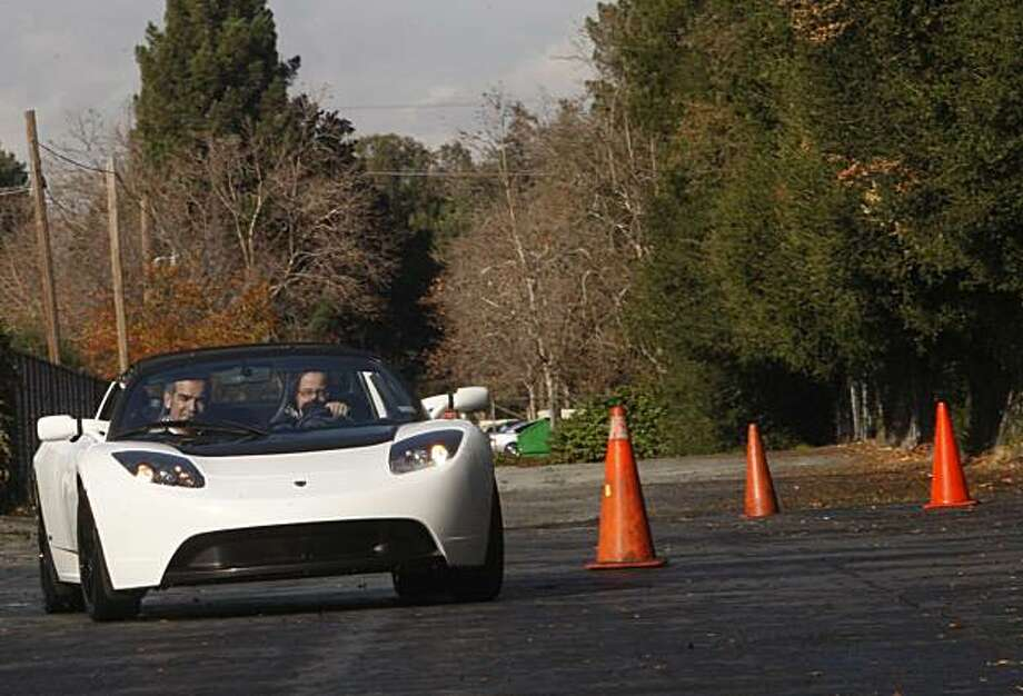 Rick Avalos (left) and Emily Ritter (right) testing a Tesla on Monday, December 14, in Menlo Park, CA.  This car will be driven cross country to the Detroit Auto Show. Photo: Liz Hafalia, The Chronicle