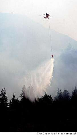 A helicopter drops water on a ridge along Highway 1 in the Big Sur, Calif., fire area on Wednesday July 2, 2008 Photo by Kim Komenich / The Chronicle Photo: Kim Komenich, The Chronicle