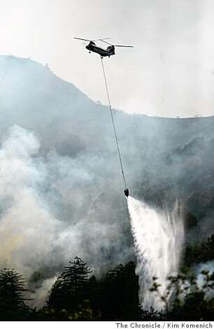 A helicopter drops water near Pico Blanco as firefighters try to gain control of the Basin Complex fire at Big Sur on Thursday, July 3, 2008.Photo by Kim Komenich / The Chronicle Photo: Kim Komenich, The Chronicle