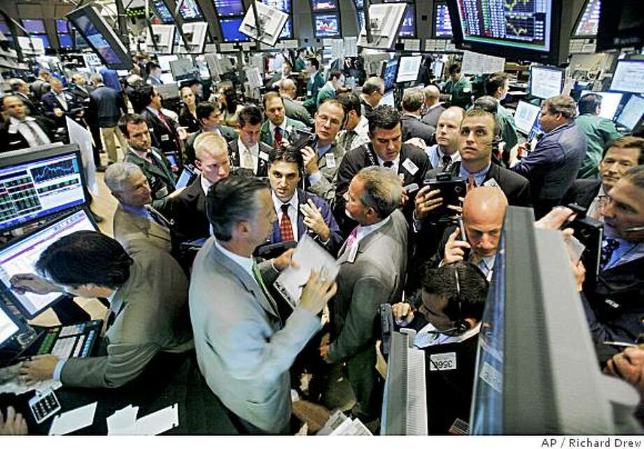 Traders crowd the post that handles Visa on the floor of the New York Stock Exchange, Friday June 27, 2008. Wall Street has suffered another big loss, with the Dow Jones industrials falling more than 100 points amid worries about high oil prices and further fallout from the credit crisis. (AP Photo/Richard Drew) Photo: Richard Drew, AP