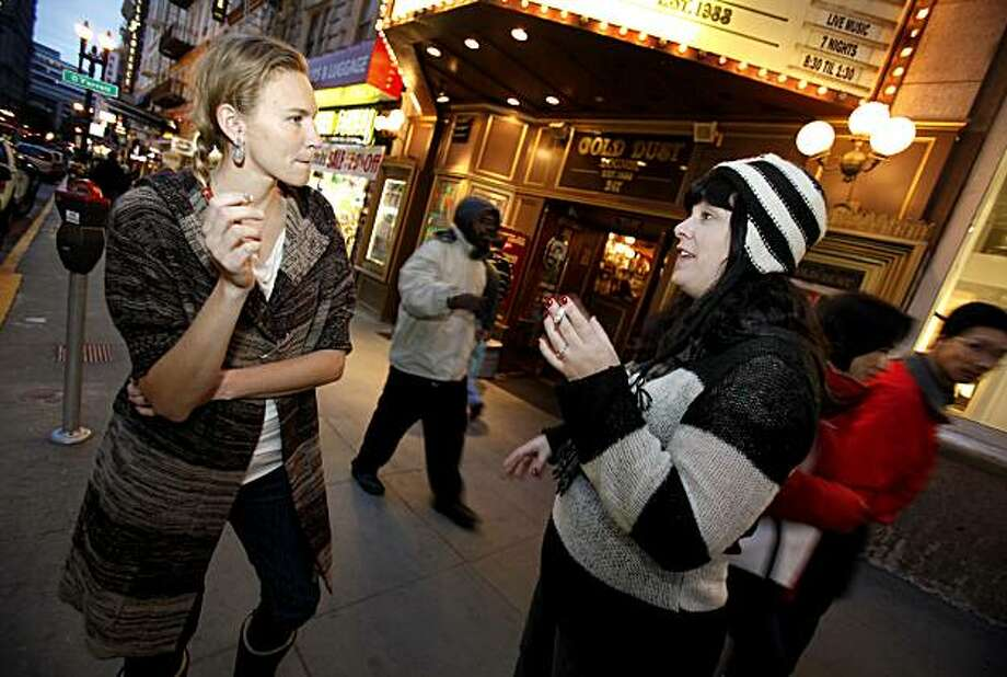 Megan Gomes (left) and Shannon Friend stood on a busy Powell Street near Union Square for a cigarette break in between shopping for Christmas presents. Photo: Brant Ward, The Chronicle