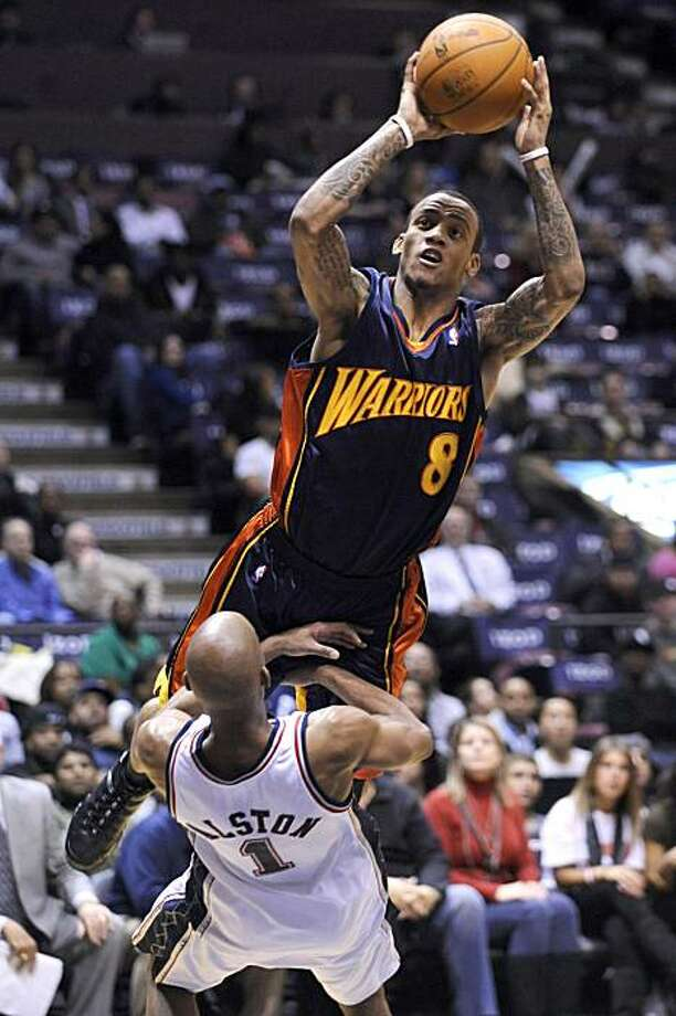 Golden State Warriors' Monta Ellis (8) lands on New Jersey Nets' Rafer Alston as he puts up a shot during the fourth quarter of an NBA basketball game Wednesday, Dec. 9, 2009 in East Rutherford, N.J. Ellis was called for a offensive foul on the play. The Warriors beat the Nets 105-89. (AP Photo/Bill Kostroun) Photo: Bill Kostroun, AP
