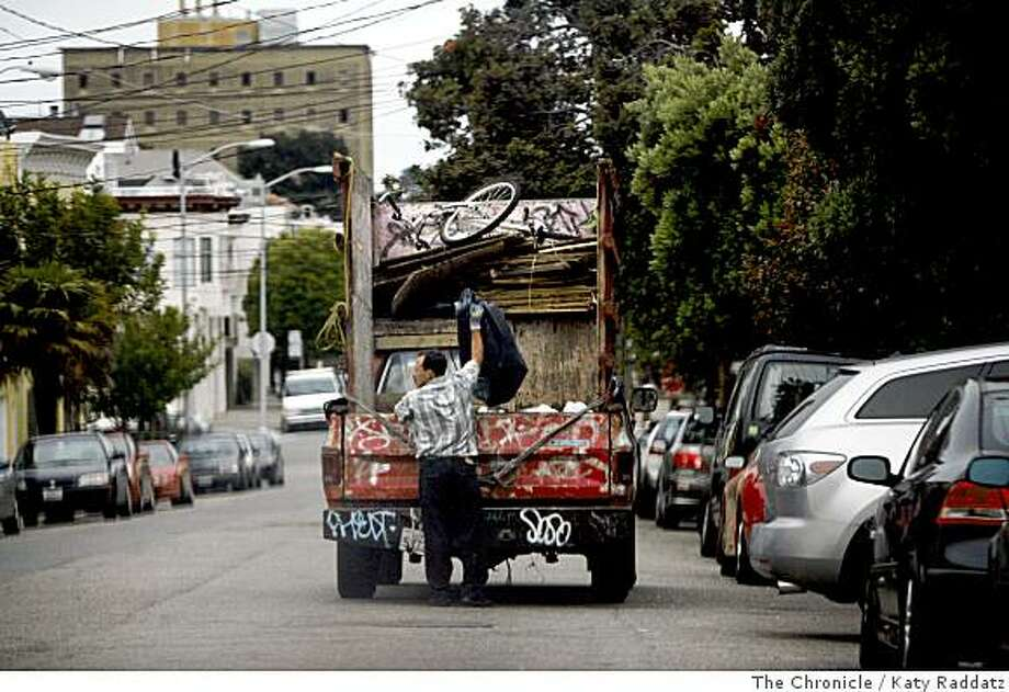 One man of a three-man crew loads recycleables from a residential bin on Duncan St. in Noe Valley into a truck in San Francisco, Calif. on Sunday,  June 29, 2008.Photo by Katy Raddatz / The Chronicle Photo: Katy Raddatz, The Chronicle