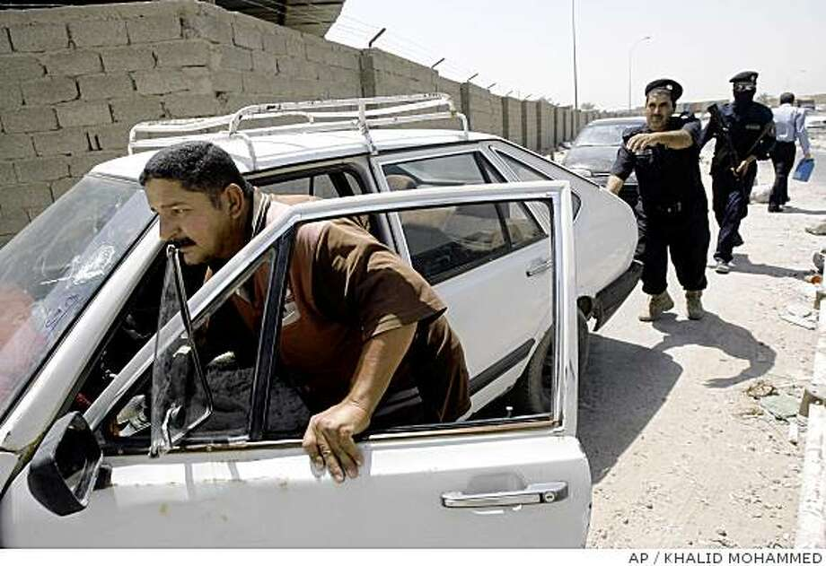 Iraqi police officers help a man push his car as he queues at a gas station in Baghdad, Iraq, Sunday, June 29, 2008. Several major oil companies are expected to announce next week contracts to start servicing the Iraqi oil infrastructure. (AP Photo/Khalid Mohammed) Photo: KHALID MOHAMMED, AP