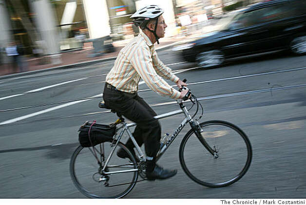 A man in a dress shirt and slacks rides his bike on Market St. in San Francisco, Calif. on Tuesday, June 25, 2008.  Photo by Mark Costantini  /  The Chronicle. Photo: Mark Costantini, The Chronicle