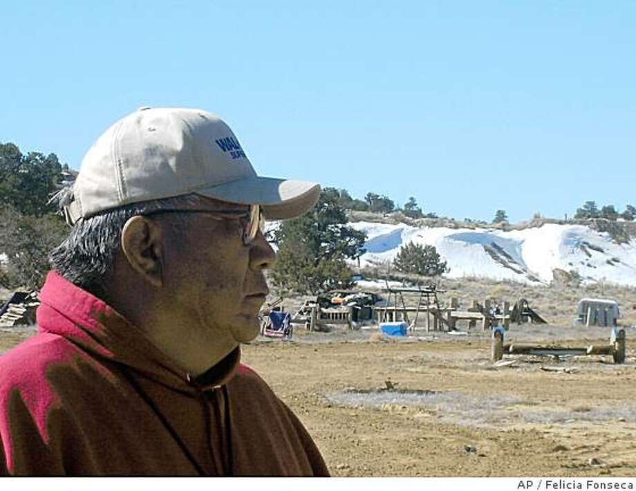 ** ADVANCE FOR MONDAY, JUNE 23 **Teddy Nez stands on his property adjacent to the Northeast Church Rock Mine in northwestern New Mexico on March 12, 2008. Behind him is a 50-foot uranium waste pile from mining operations. The former uranium mine is the most contaminated on the 27,000 square-mile reservation. The U.S. Environmental Protection Agency recently released a 5-year plan to clean up contamination on the reservation. (AP Photo/Felicia Fonseca) Photo: Felicia Fonseca, AP