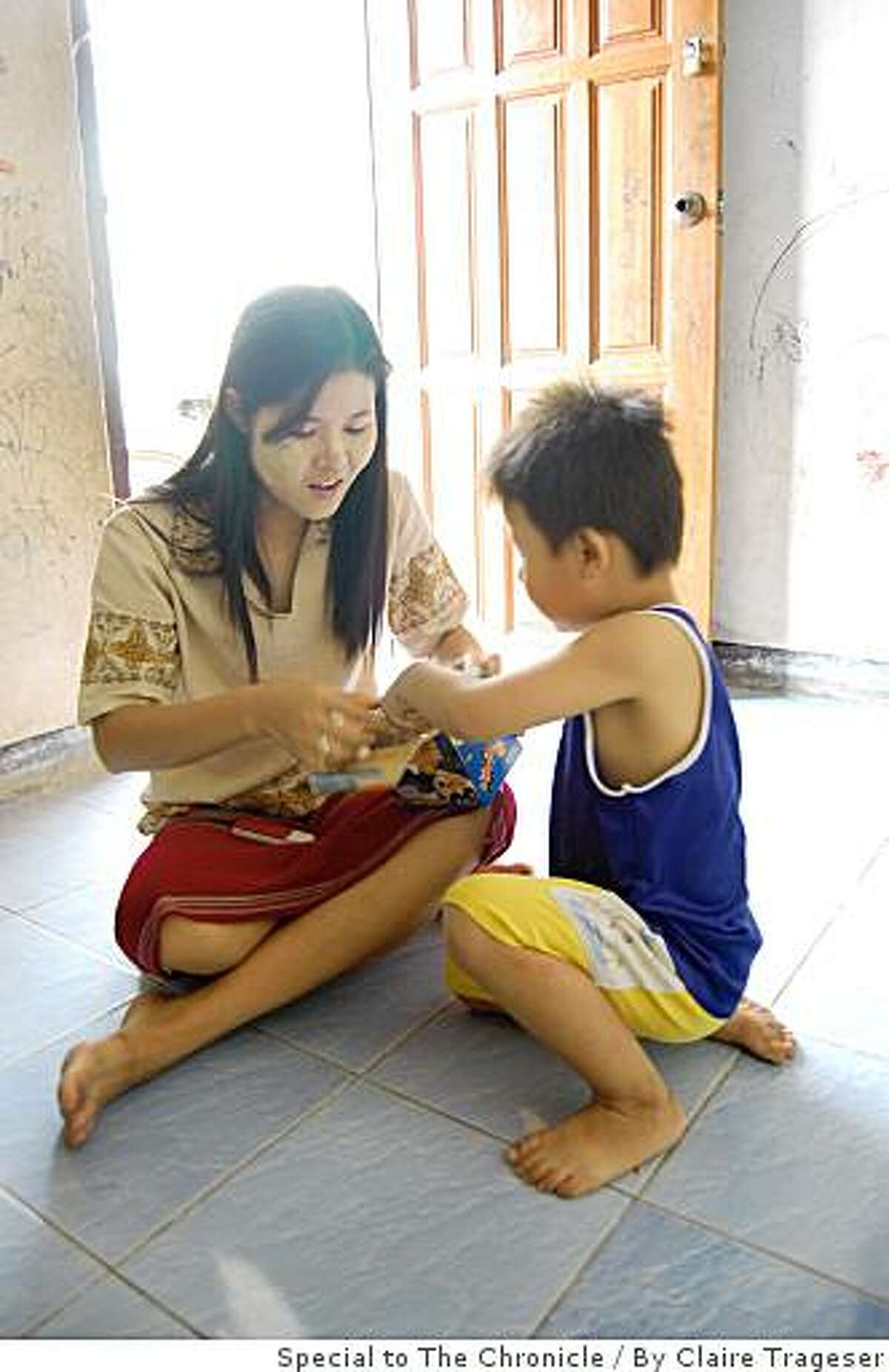Nid Paw, a Burmese refugee who hopes to settle in the United States this year, unwraps a new toy for her son, Saw, as they sit on the floor of their apartment in Mae Sot, Thailand.