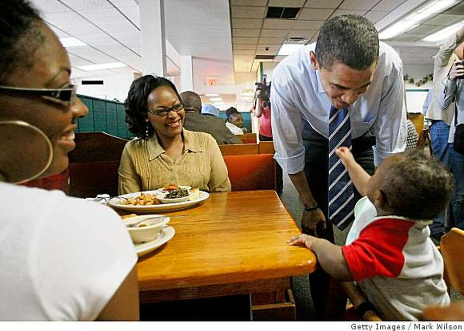 GREENSBORO, NC,: Democratic presidential hopeful Sen. Barack Obama of Illinois  talks with 7-month-old Aedyn Buchanon while his mother Domonique Burst (L) and Florine Horton sit nearby during a visit to Stephanies II Home Style Restaurant May 5, 2008 in Greensboro, North Carolina. Indiana and North Carolina go to the polls May 6. (Photo by Mark Wilson/Getty Images) Photo: Getty Images