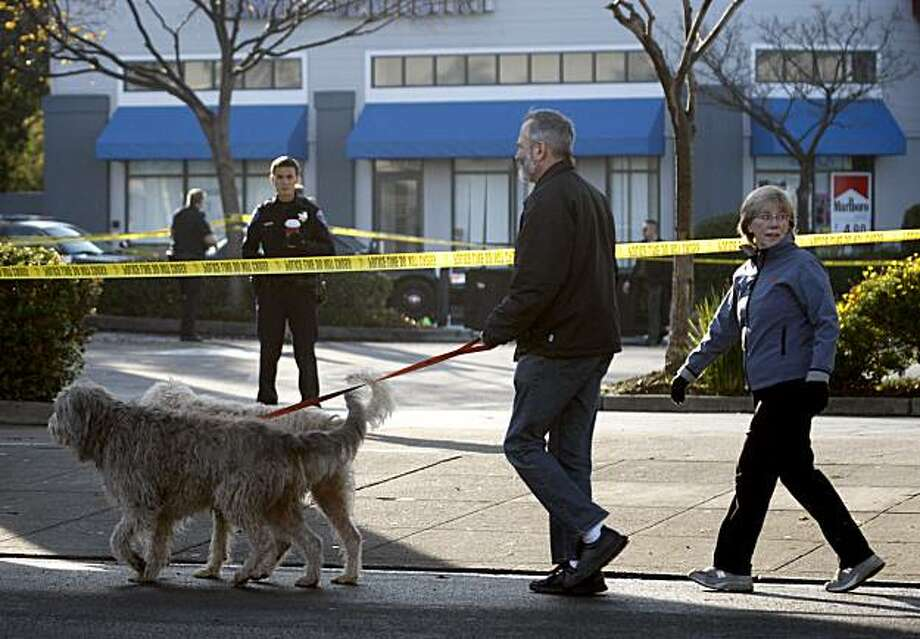 George Van Treeck and Jen Tellier walk their dogs Bonnie and Clyde past the crime scene after police officers shot and killed a police dog named Billy after he attacked the officer responding to a burglary at the Coast Guard Recruiting Center in Alameda George Van Treeck and Jen Tellier walk their dogs Bonnie and Clyde past the crime scene after police officers shot and killed a police dog named Billy after he attacked the officer responding to a burglary at the Coast Guard Recruiting Center in Alameda, Calif., on Thursday, Dec. 17, 2009. Police took the suspected burglar into custody. Billy is the second Alameda police canine to die this year. Photo: Paul Chinn, The Chronicle