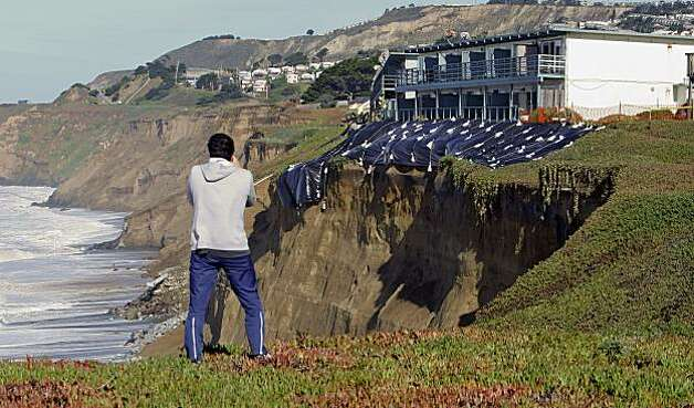 Tom Miyasato of Pacifica stops to take a photo after residents were ordered to evauate the apartment building at 330 Esplanade Drive inPacifica, Ca. on Thursday December 17, 2009, as the cliff it is perched upon is slowly eroding leaving only 10 feet of land between the ocean and the structure. Photo: Michael Macor, The Chronicle