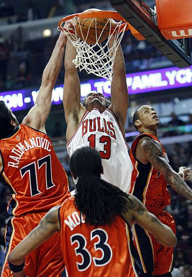 Chicago Bulls' Joakim Noah (13) goes up for a dunk against Golden State Warriors' Vladimir Radmanovic (77) of Serbia, Monta Ellis, right, and Mikki Moore during the first quarter of an NBA basketball game in Chicago, Friday, Dec. 11, 2009. (AP Photo/Nam Y. Huh) Photo: Nam Y. Huh, AP