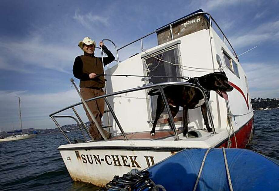 Weissleder and Pico prepare to go back to the mainland. Myles Weissleder uses a floating office, a houseboat anchored off Sausalito, for his technology business.  He regularly commutes to the houseboat from a tender with his trusty dog Pico. Photo: Brant Ward, The Chronicle