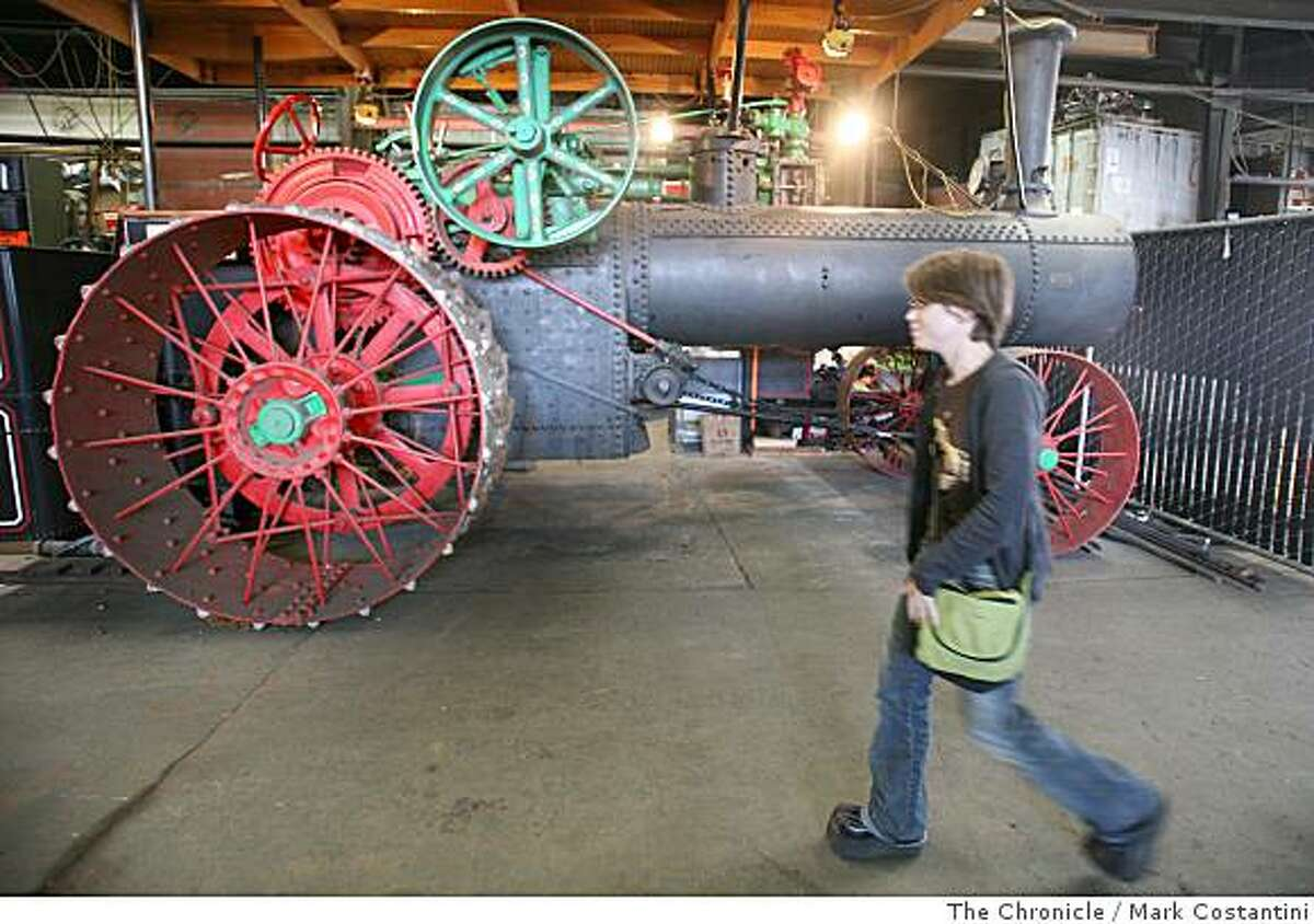 With a steamtrain in the background, a woman enters a party in Oakland, Calif. on Sunday, June 29, 2008 at Kinetic Steamworks, which has just completed work on a steamboat that will be soon shipped to New York . Photo by Mark Costantini / The Chronicle.