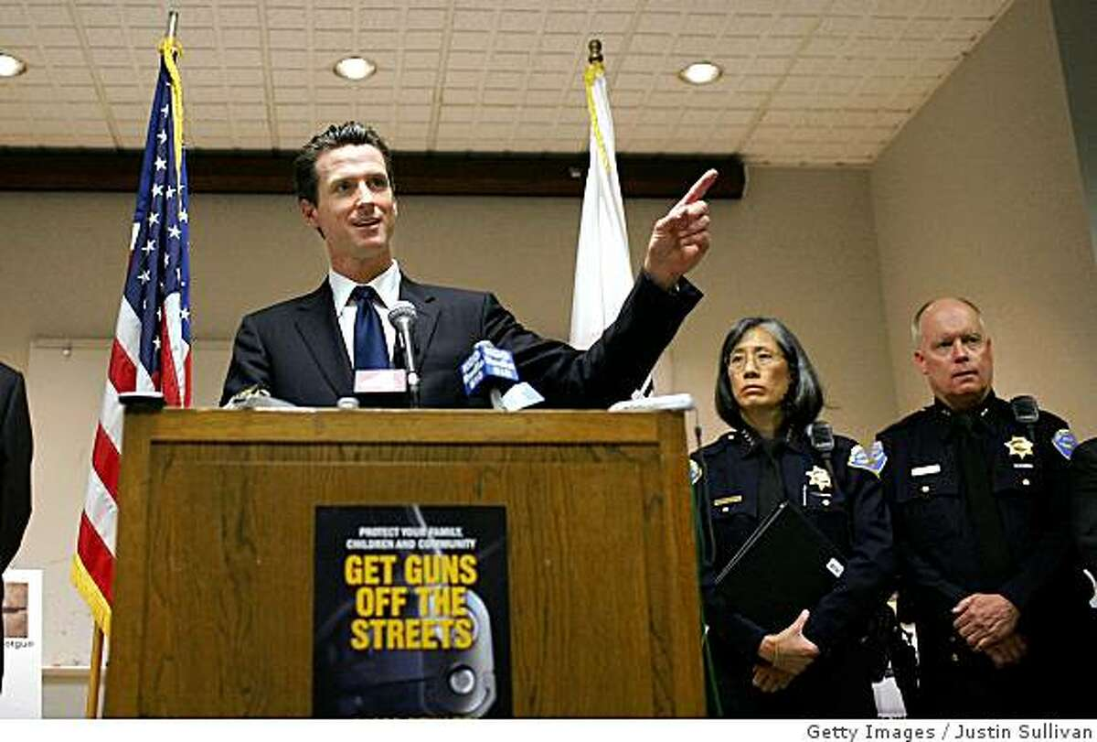 SAN FRANCISCO - JUNE 27: Flanked San Francisco Police Chief Heather Fong, center, and Deputy Chief Kevin Cashman, San Francisco mayor Gavin Newsom, left, speaks during a press conference where he announced new anit-gun initiatives June 27, 2008 in San Francisco, California. A day after the U.S. Supreme Court ruled that American citizens have the right to own firearms and just hours after the National Rifle Association filed a suit against the city to overturn the city's gun ban in public housing, San Francisco mayor Gavin Newsom announced new anti-gun initiatives to strengthen the city's anti-gun laws. (Photo by Justin Sullivan/Getty Images)