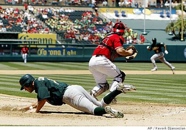 Oakland Athletics' Bobby Crosby, left, scores a run on a throwing error by Los Angeles Angels right fielder Gary Matthews Jr. as Angels' catcher Mike Napoli, center, prepares to throw to third base to throw out Athletics' Emil Brown, right, during the fourth inning of a baseball game in Anaheim, Wednesday July 2, 2008. Crosby scored on Brown's double. (AP Photo/Kevork Djansezian) Photo: Kevork Djansezian, AP