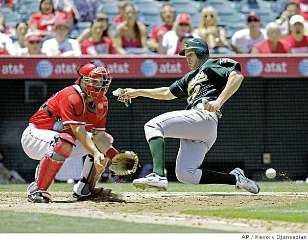 Oakland Athletics' Bobby Crosby, right, scores a run on a double by Emil Brown as Angels catcher Mike Napoli prepares to catch the throw during the fourth inning of a baseball game in Anaheim, Calif., Wednesday, July 2, 2008. (AP Photo/Kevork Djansezian) Photo: Kevork Djansezian, AP
