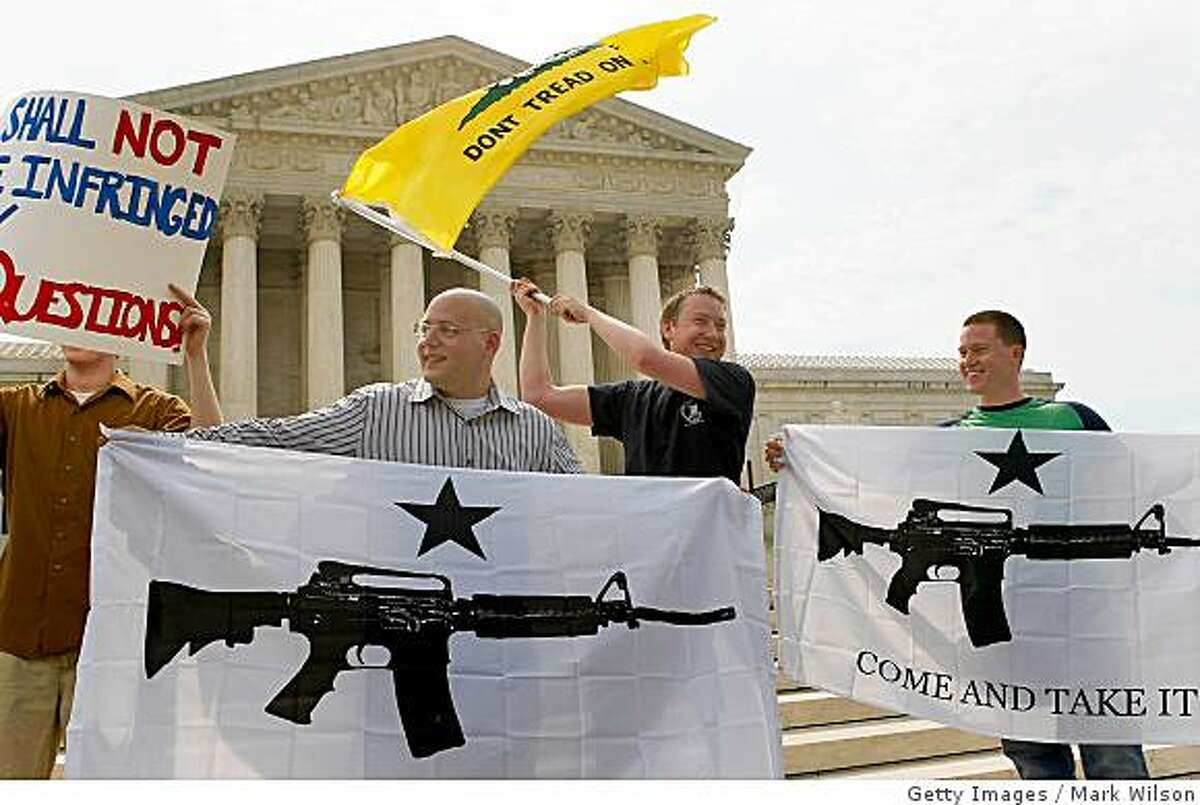 WASHINGTON - JUNE 26: Gun rights activists Ariel Sarousi (2nd L) Craig Burgers and Steve Bierfeld (R), all of Arlington, Virginia, react to the U.S. Supreme Court's decision on the District of Columbia's gun ban, June 26, 2008 in Washington, DC. The high court struck down the Districts gun ban and said that Americans have a right to own guns for self defense and hunting, (Photo by Mark Wilson/Getty Images)