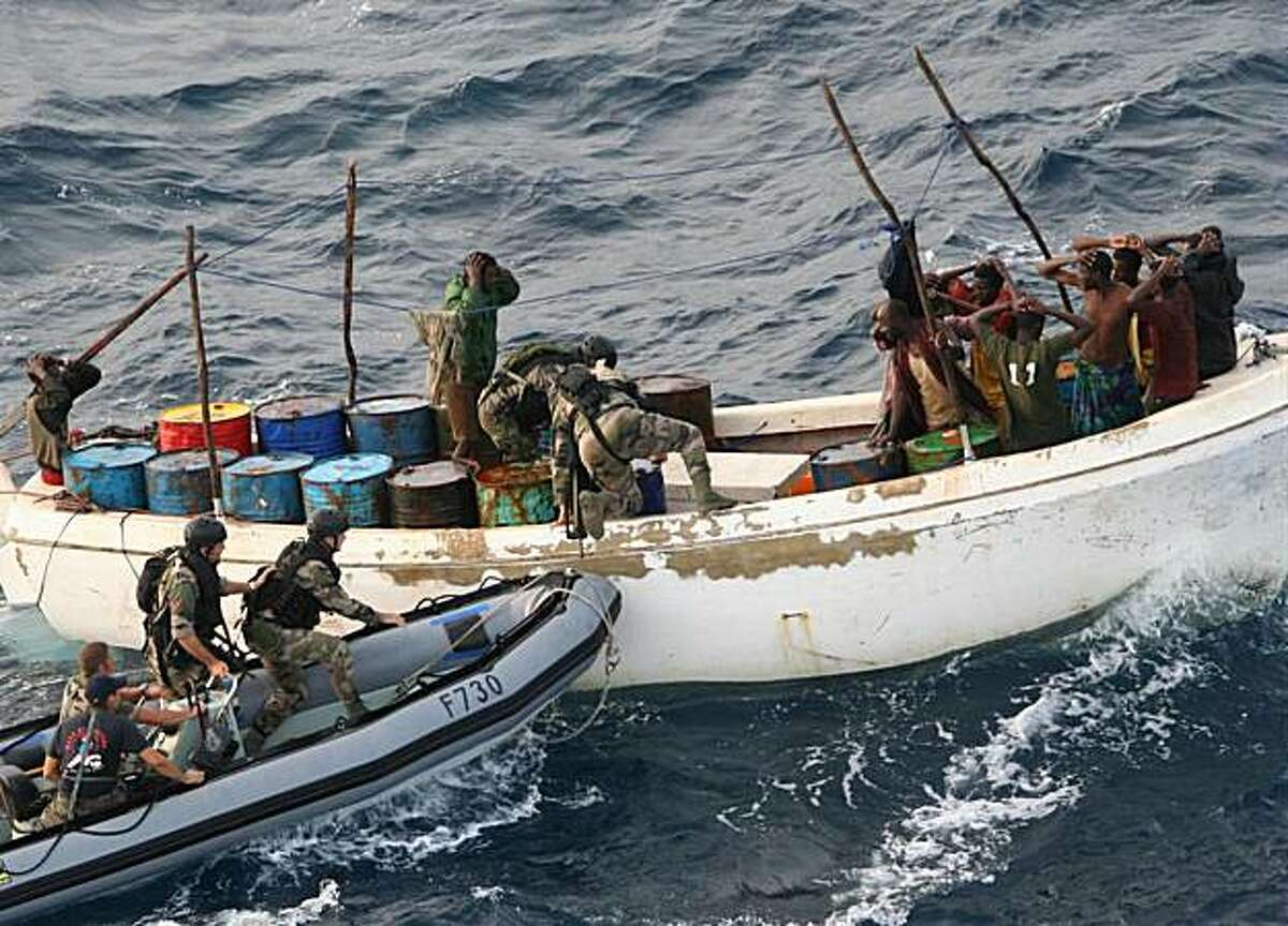**ADVANCE FOR MONDAY, DEC. 6** FILE - This Thursday Nov. 12, 2009 file photo released by the French Army shows French soldiers arresting suspected pirates off Somalia. The influx of millions of dollars in ransoms has changed life in some coastal communities in Somalia, driving prices up and creating a schism between the pirate-haves and have-nots. As piracy ramps up again with the end of the monsoon season, the lifestyle of the pirates, with big houses, fast cars and easy drugs, is decried by both religious leaders and ordinary villagers. (AP Photo/French Army/ECPAD, File) **NO SALES**