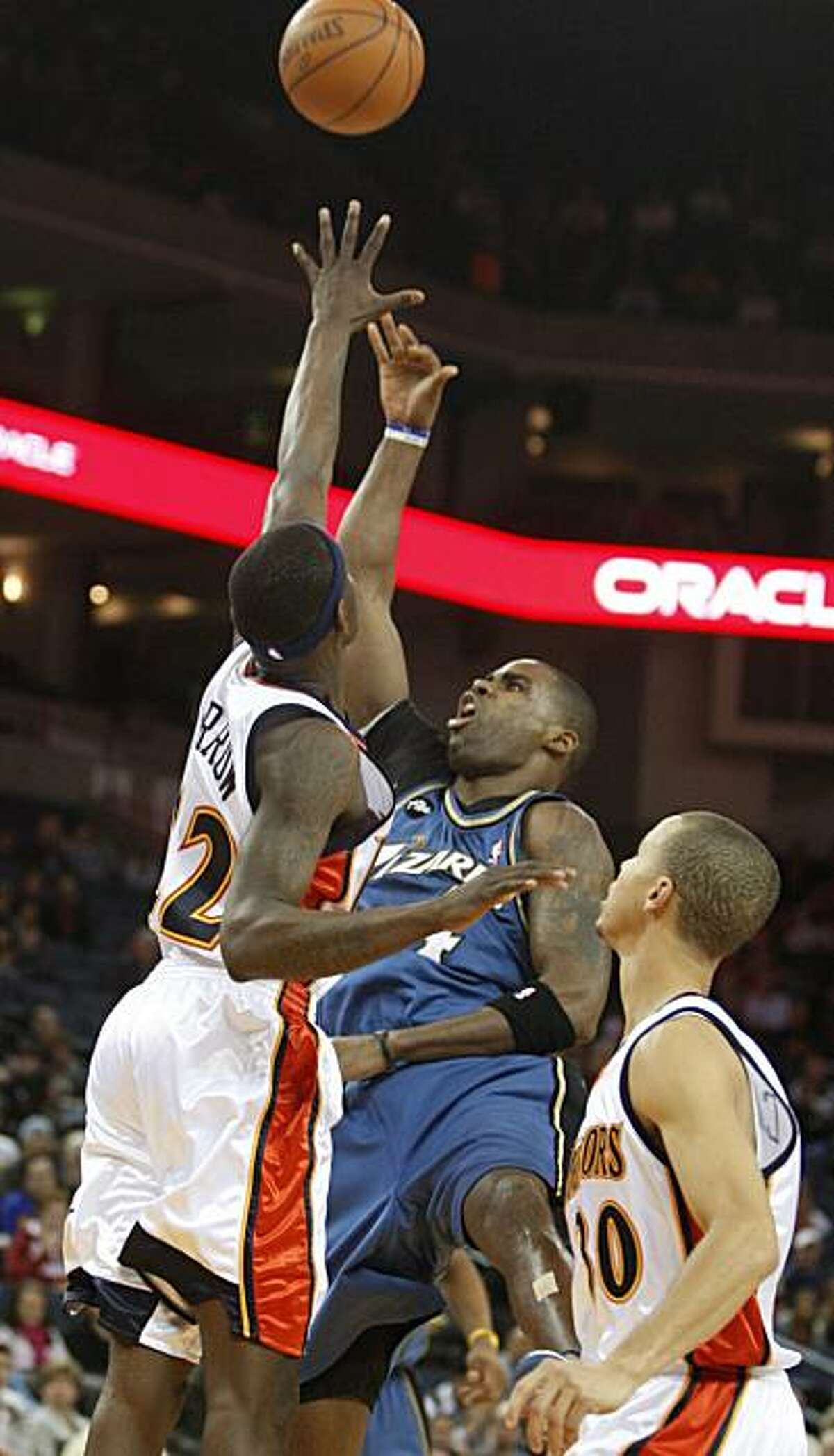 Washington Wizards' Antawn Jamison, center, takes a shot between Golden State Warriors' Anthony Morrow, left, and Stephen Curry during the first half of an NBA basketball game Friday, Dec. 18, 2009, in Oakland, Calif. (AP Photo/Ben Margot)