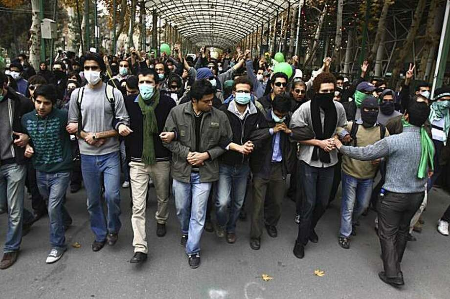 """This photo, taken by an individual not employed by the Associated Press and obtained by the AP outside Iran shows pro-reform Iranian students, marching during their protest at the Tehran University campus in Tehran, Iran, Monday, Dec. 7, 2009. Security forces and pro-government militiamen clashed with protesters shouting """"death to the dictator"""" outside Tehran University on Monday, beating men and women with batons and firing tear gas, on a day of nationwide student demonstrations, witnesses said. (AP Photo) EDITORS NOTE AS A RESULT OF AN OFFICIAL IRANIAN GOVERNMENT BAN ON FOREIGN MEDIA COVERING SOME EVENTS IN IRAN, THE AP WAS PREVENTED FROM INDEPENDENT ACCESS TO THIS EVENT Photo: Stringer, AP"""