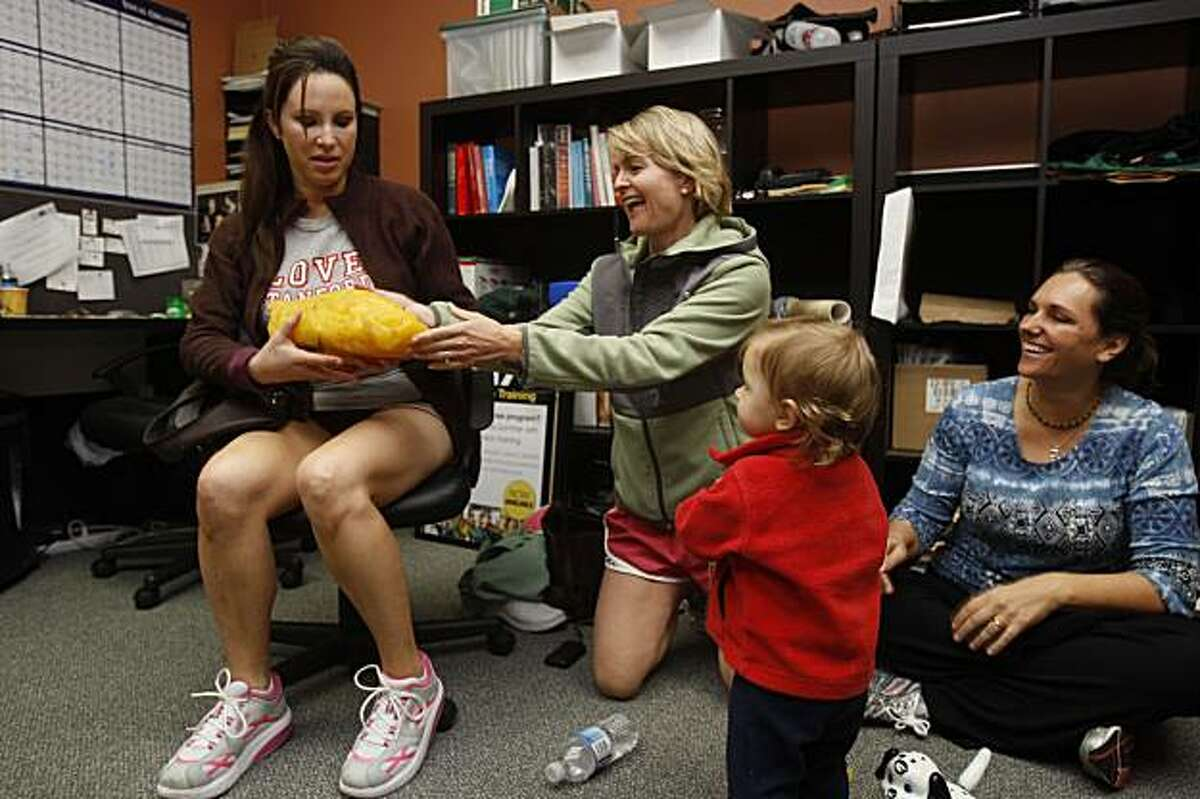 Cecilia Marosi-Hopkins (left) takes a replica of five pounds of fat from Gaylene Parker (back, middle) as Mia Gates (right) smiles on at Fitness 101 gym in Menlo Park, Calif., on Monday, November 16, 2009. Five people enlisted to embark on a 6-week diet and fitness program