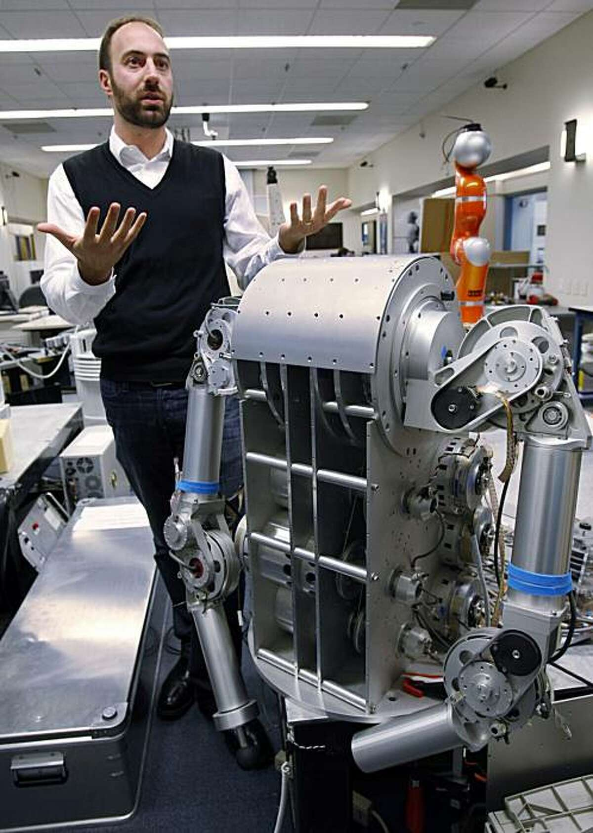 Ryan Calo of the Stanford Center for Internet and Society at the Stanford Law School stands next to a robot that is being built for medical applications at Stanford University's Artificial Intelligence Laboratory in Palo Alto.