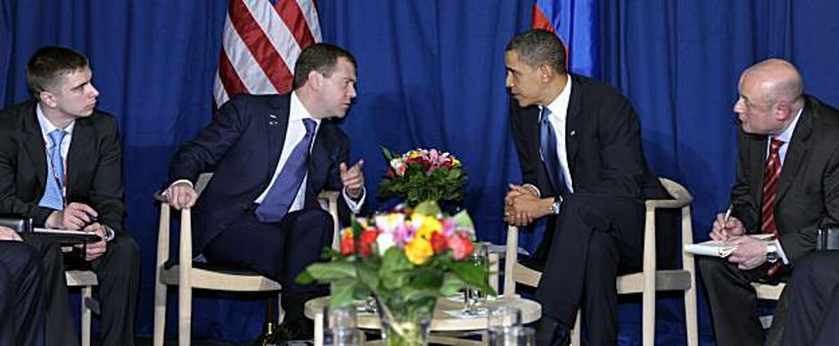 With translators on either side, President Barack Obama and Russian President Dmitry Medvedev talk during a meeting at the United Nations Climate Change Conference at the Bella Center in Copenhagen, Denmark, Friday, Dec. 18, 2009. (AP Photo/Susan Walsh)