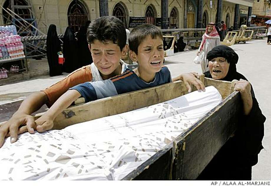 The body of Iraqi army soldier Ahmed Mohan lies in a coffin as his sons Haider and Mohdaffer and his mother mourns, in the holy city of Najaf, 160 kilometers (100 miles) south of Baghdad, Iraq, on Tuesday, June 24, 2008. Mohad was killed in Sadr city, the family said.(AP Photo/Alaa al-Marjani) Photo: ALAA AL-MARJANI, AP