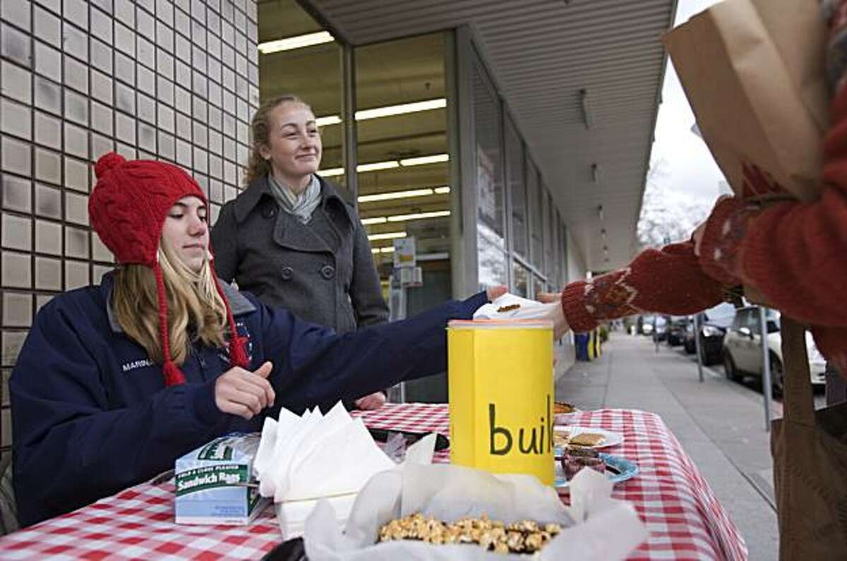 Piedmont High School students Marina Fennell and Laura Watry, from left, sell baked goods outside the Ace Hardware store on Grand Ave. in Piedmont, Calif., to raise money for the Build On Foundation. Piedmont has many school fundraisers and other community-oriented events throughout the year.