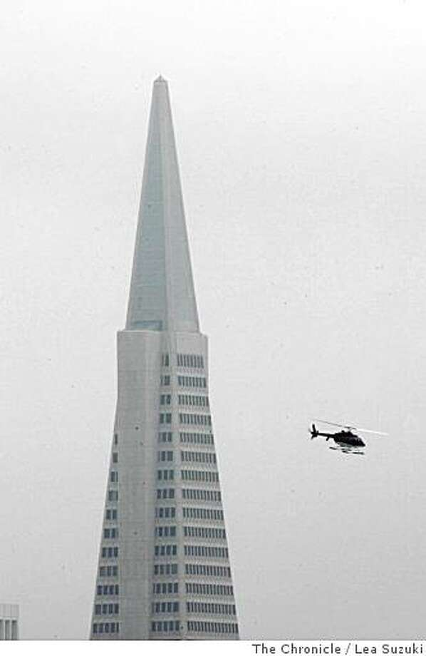 A helicopter passes the tip of the Transamerica Pyramid on a hazy day in San Francisco, Calif. on Monday June 23, 2008. Photo By Lea Suzuki/ The Chronicle Photo: Lea Suzuki, The Chronicle