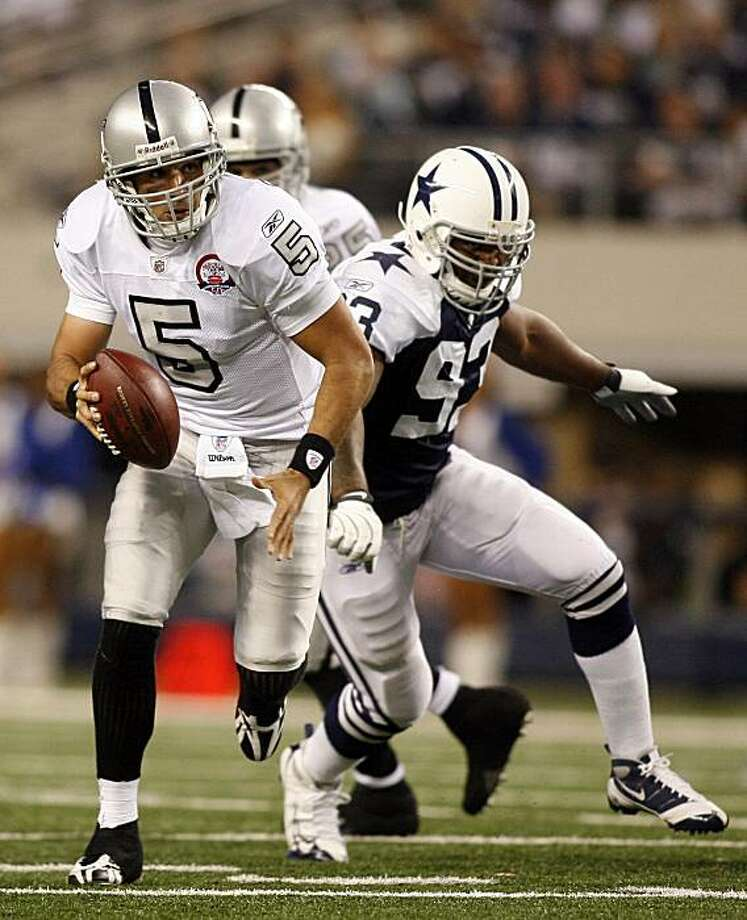 In this photo taken on Thursday, Nov. 26, 2009, Oakland Raiders quarterback Bruce Gradkowski (5) runs away from Dallas Cowboys linebacker Anthony Spencer (93) during an NFL football game in Arlington, Texas. Gradkowski grew up cheering for the Pittsburgh Steelers. As a pro, he's had little success against his hometown team, losing both starts heading into this week's meeting between the Raiders and Steelers. (AP Photo/Mike Stone) Photo: Mike Stone, AP