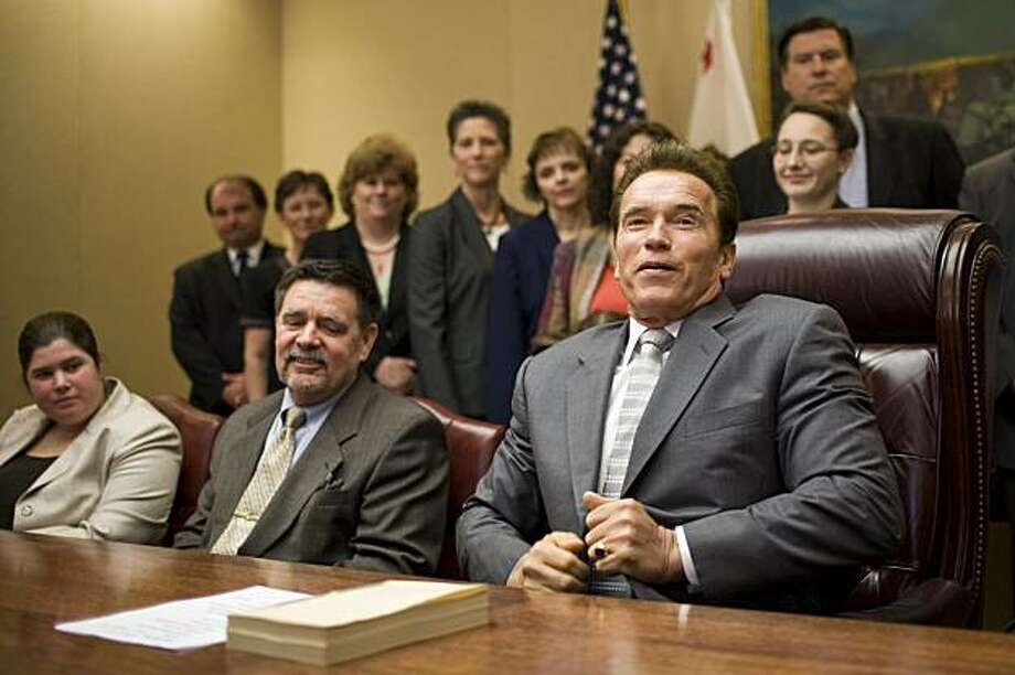 SACRAMENTO, CA - JULY 28:   California Governor Arnold Schwarzenegger (R) smiles after signing the state's budget solution on July 28, 2009 in Sacramento, California.  The state's $24 billion budget includes $16.1 billion in spending reductions, and Schwarzenegger used line-item vetos to eliminate another $489 million in spending not approved by the legislature. (Photo by Max Whittaker/Getty Images) Photo: Max Whittaker, Getty Images