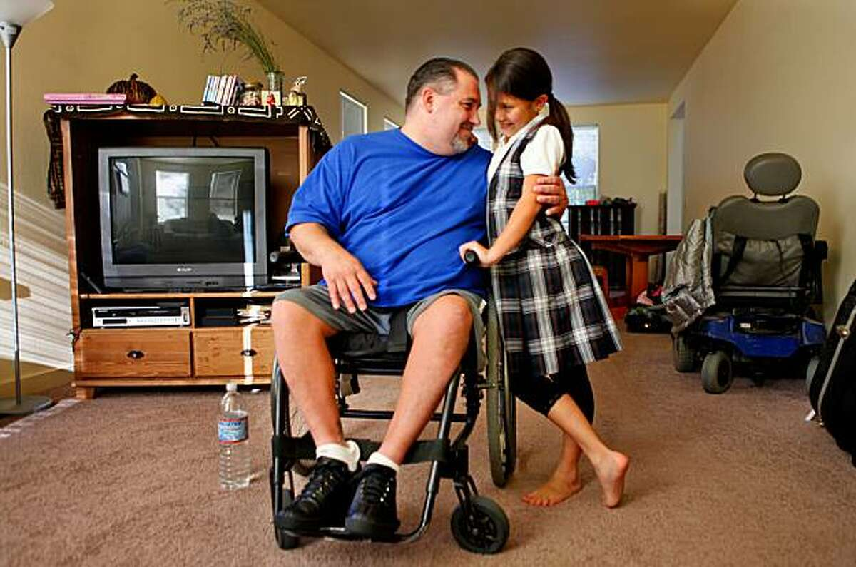 Joshua Poole plays with his daughter Kathleen at their home, Wednesday Nov. 18, 2009, in Fairfax, Calif.