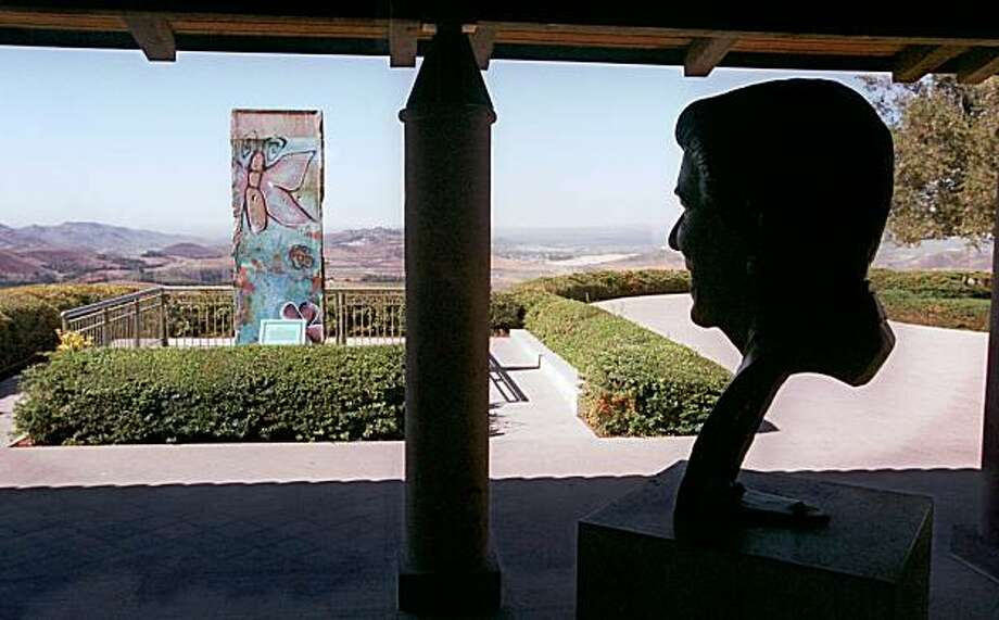 SIMI VALLEY, Calif.  -- A bust of former U.S. President Ronald Reagan, by the artist Donald Winton, appears to gaze out upon a section of the Berlin Wall which resides on the grounds of the Ronald Reagan Presidential Library in Simi Valley, Calif., Oct. 13, 1999. The section ofwall was donated to the library in April 1990. (AP Photo/Chris Pizzello) Photo: Chris Pizzello, AP
