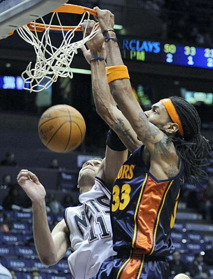 Golden State Warriors' Mikki Moore, right, dunks the ball over New Jersey Nets' Brook Lopez during the fourth quarter of an NBA basketball game Wednesday, Dec. 9, 2009 in East Rutherford, N.J. The Warriors beat the Nets 105-89. (AP Photo/Bill Kostroun) Photo: Bill Kostroun, AP