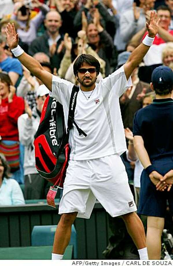 Serbia's Janko Tipsarevic celebrates as he leaves the court after beating US Andy Roddick during their 2008 Wimbledon championships tennis match against  at The All England Tennis Club in southwest London, on June 26, 2008. Tipsarevic won 6-7, 7-5, 6-4, 7-6.      AFP PHOTO / Carl De Souza (Photo credit should read CARL DE SOUZA/AFP/Getty Images) Photo: CARL DE SOUZA, AFP/Getty Images