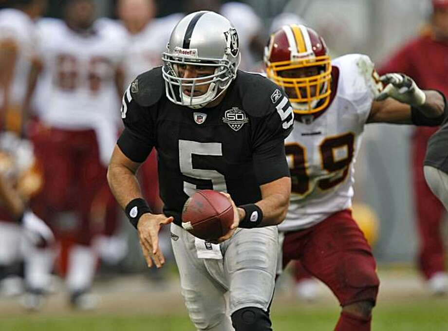 Raiders quarterback Bruce Gradkowski  hands of the ball in the first half Sunday in Oakland. Photo: Lacy Atkins, The Chronicle