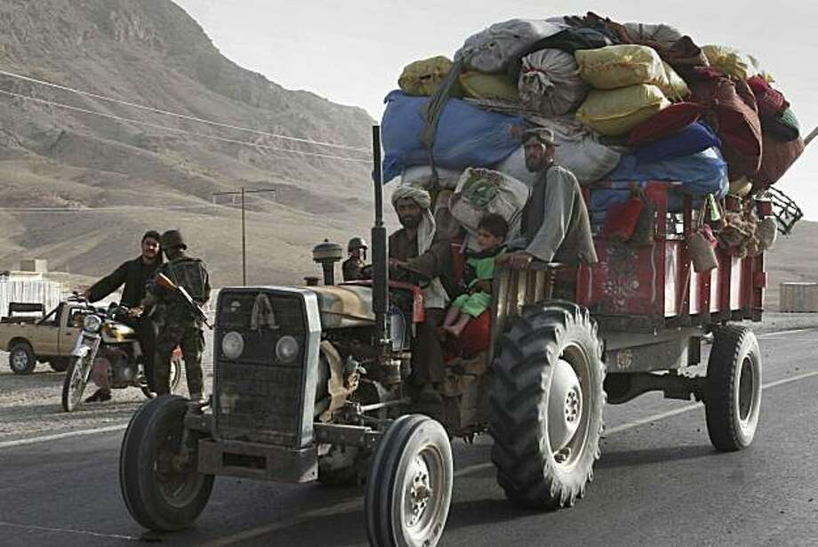 "Afghans carry their belongings on a tractor as they leave the Arghandab district, which is partly controlled by the Taliban militants, for the city of Kandarhar province, south of Kabul, Afghanistan, Tuesday, June 17, 2008. ""Last night the people were afraid, and families on tractors, trucks and taxis fled the area,"" said Mohammad. ""Small bridges inside the villages have been destroyed."" (AP Photo/Allauddin Khan) Photo: Allauddiin Khan, AP"