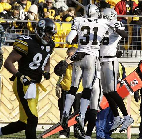 Pittsburgh Steelers receiver Hines Ward, left, trots back to his bench as Oakland Raiders' Hiram Eugene (31) celebrates with teammate Stanford Routt (26) after intercepting a pass intended for Ward in the end zone during the second quarter of an  NFL football game  in Pittsburgh, Sunday, Dec. 6, 2009. (AP Photo/Gene J. Puskar) Photo: Gene J. Puskar, AP
