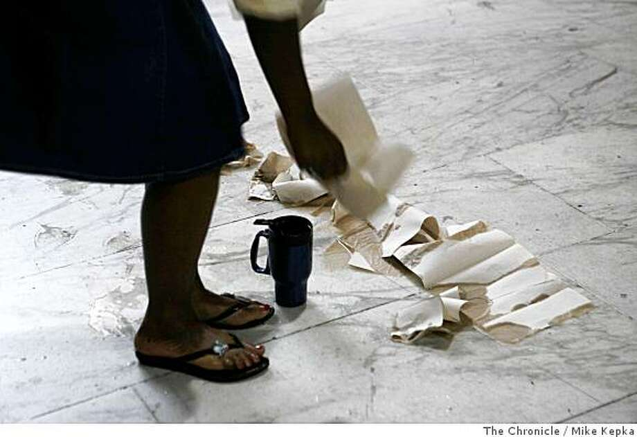 BART director, Lynette Sweet cleans a spilled water that came froma tip-proof coffee mug she hopes might be a solution to the coffee ban on commuter trains on Thursday June 19, 2008 in San Francisco, Calif. Photo by Mike Kepka / The Chronicle Photo: Mike Kepka, The Chronicle