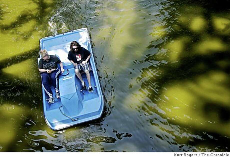 Hillary Reid  and Evan King of San Francisco in a paddle boat made their way around Stow lake in Golden Gate Park  on Tuesday  , June 24,  2008 in San Francisco, Calif  Photo by Kurt Rogers / The Chronicle. Photo: Kurt Rogers, The Chronicle