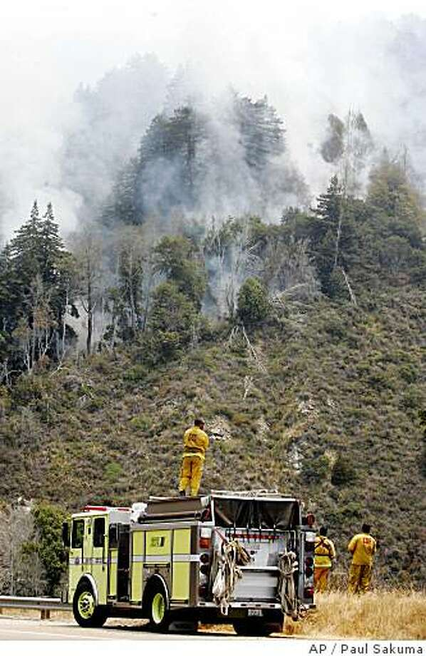 Firefighters watch a wildfire burn in Big Sur, Calif., in Monterey County, Tuesday, June 24, 2008. The fire near the coast south of Big Sur was only 3 percent contained. It has consumed about 11 square miles acres since it was first reported Monday.  (AP Photo/Paul Sakuma) Photo: Paul Sakuma, AP