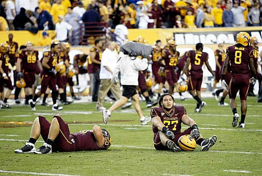 Arizona State's Lawrence Guy, left, and Saia Falahola sit on the field after losing an NCAA college football game against Arizona, Saturday, Nov. 28, 2009, in Tempe, Ariz. Arizona won 20-17. (AP Photo/Matt York) Photo: Matt York, AP