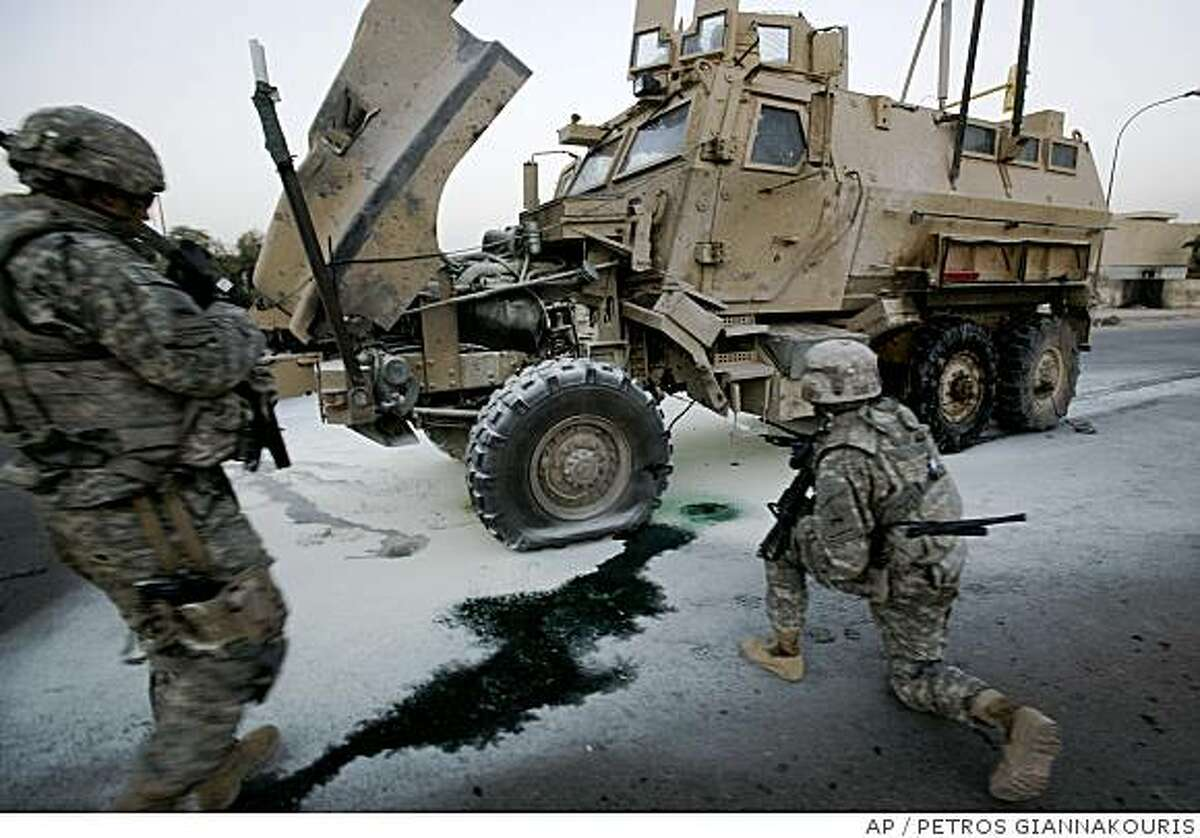 U.S. soldiers of 1-6 battalion, 2nd brigade, 1st Armored Division , inspect a damaged army vehicle (MRAP) following a roadside bomb explosion targeting an American patrol, in Al Talibiyah street, Baghdad, Iraq, on Thursday, June 19, 2008. There was no injures of the explosion the U.S. army said.(AP Photo/Petros Giannakouris)