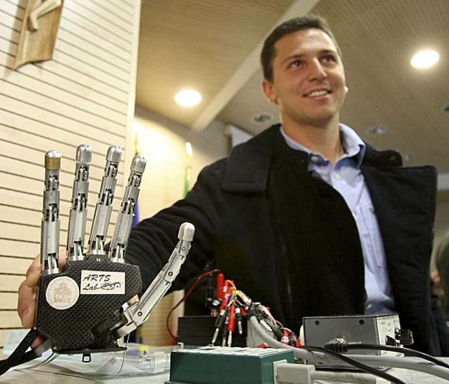 Amputee Pierpaolo Petruzziello touches a robotic hand during a press conference in Rome, Wednesday, Dec. 2, 2009. Petruzziello took part in an experiment in which a group of European scientists say they successfully connected him to the robotic hand, using electrodes to his body, allowing him to control the prosthetic with his thoughts and feel sensations in the artificial limb. The experiment lasted a month. But scientists say it marks the first time an amputee has been able to make complex movements using his mind to control a biomechanic hand connected to his nervous system. (AP Photo/Alessandra Tarantino) Photo: Alessandra Tarantino, AP