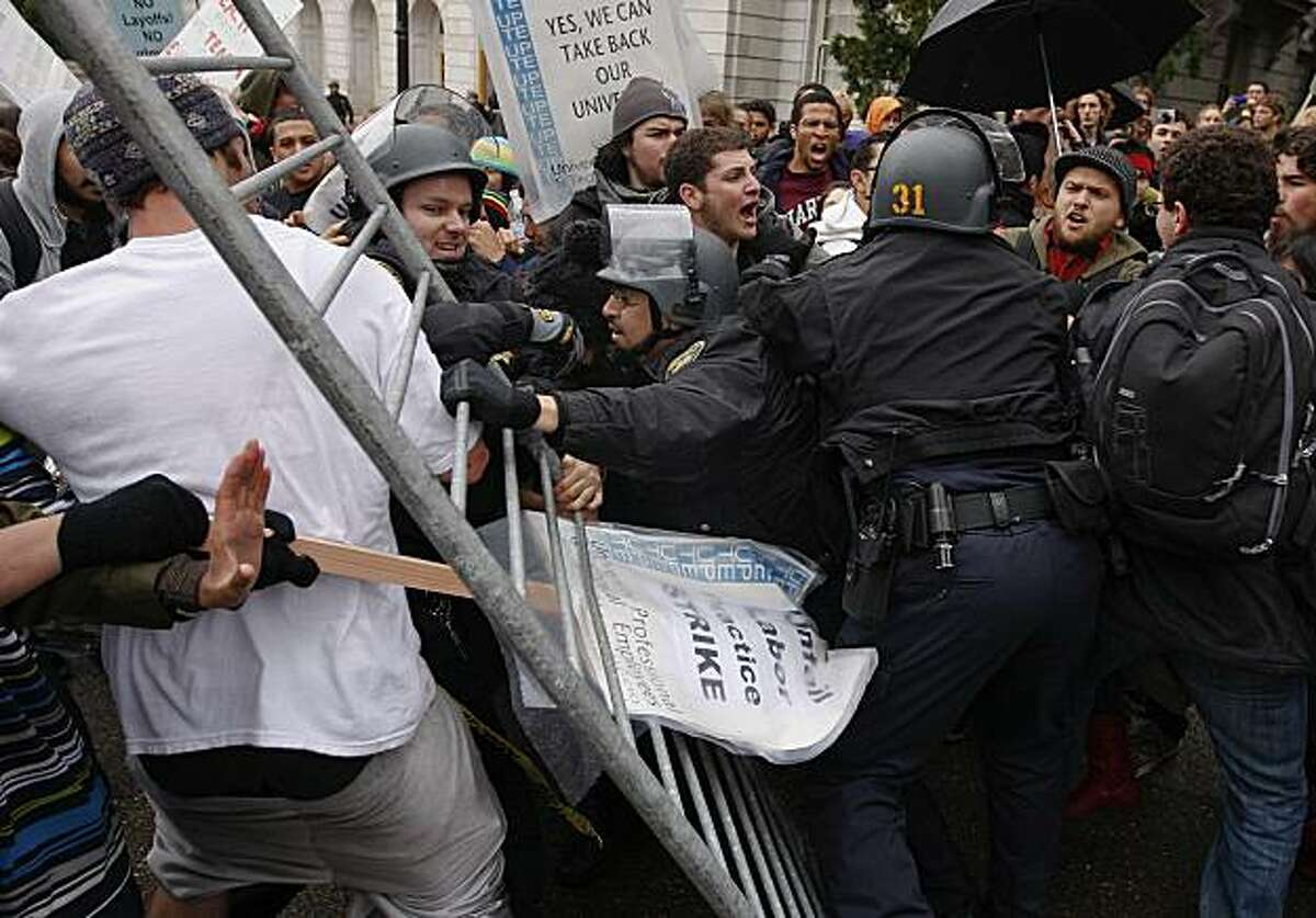 UC Police push back protesters as they move in barricades in front of Wheeler Hall. Students rallied on the UC Berkeley campus Friday to protest of pay cuts, layoffs and tuition hikes.